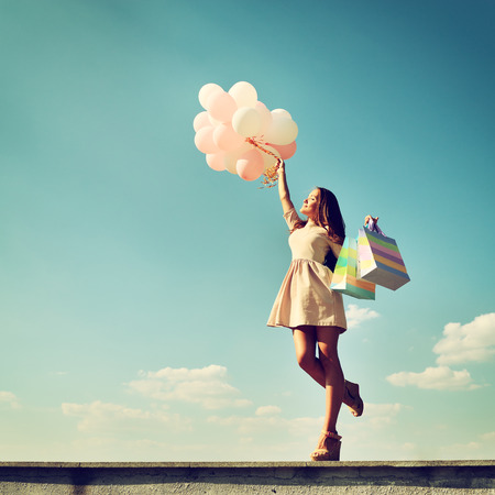 Photo pour Beautiful girl holding shopping bags and colored ballons over blue sky, toned - image libre de droit