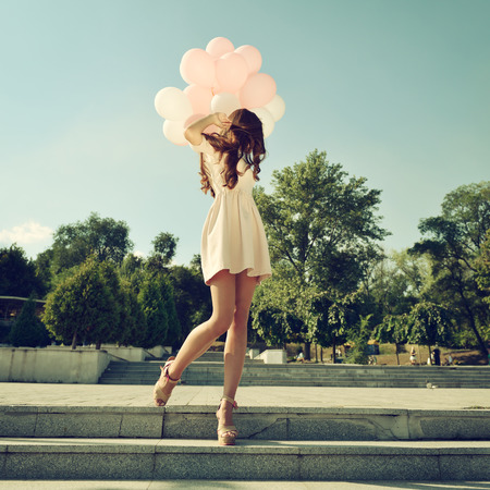 Foto de Fashion girl with air balloons steps on stairs, image toned. - Imagen libre de derechos