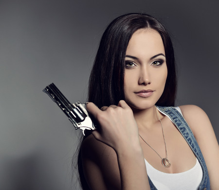 Beautiful girl with gun, studio shot.