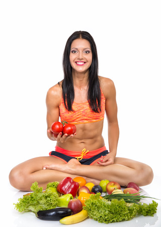 Foto für Portrait of slim fitness cherrful girl sitting in studio with set of fruit and vegetables over white background. Healthy eating, diet, fitness, weight lose concept. - Lizenzfreies Bild