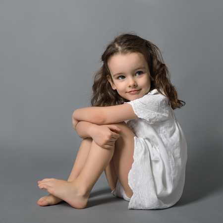 Photo for Sweet little happy girl in white dress, studio portrait over gray background - Royalty Free Image