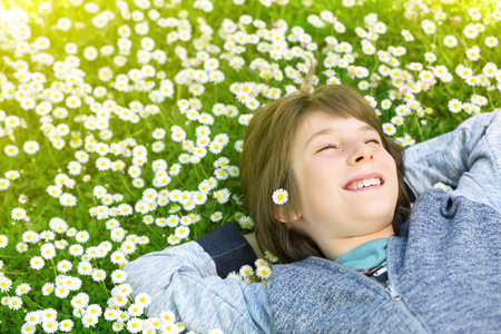 Handsome happy smiling young boy lying on summer meadow green grass with daisy. Attractive smiling teen boy posing over nature background, image toned.