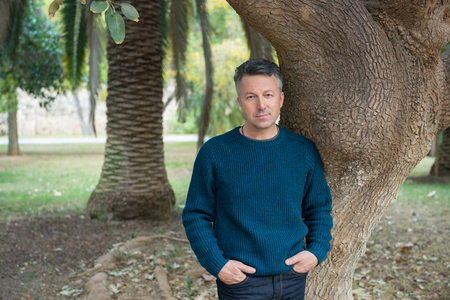 Photo pour Handsome middle-aged man in Mediterranean park with palm trees. Attractive mid adult male model posing outddor. - image libre de droit