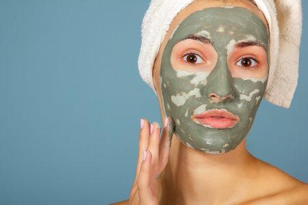 Beautiful cheerful teen girl applying facial clay mask. Beauty treatments, isolated on blue background.の写真素材