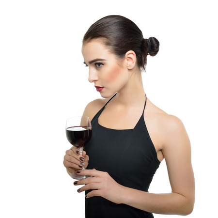Photo pour Young attractive woman holding glass of red wine. Pretty lady drinks alcoholic drink. Beautiful girl wearing black dress  with glass of wine isolated on white background. - image libre de droit