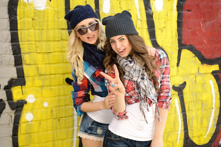 Photo pour Young pretty hipster girls having fun outdoor, summer on the street. Teenage lifestyle. Trendy modern portrait of funny beautiful teen girls over grunge wall. Two young women have fun together - image libre de droit