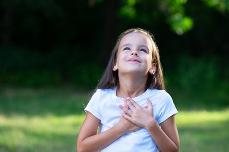 Photo pour Little girl looking up to at sky with hands on chest, summer nature outdoor. Happy smiling kid feels grateful, wishes dream come true - image libre de droit