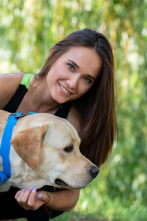 Photo for Cheerful pretty young woman sitting and hugging her dog at river bank in summer park - Royalty Free Image