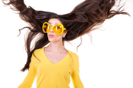 Foto de Happy smiling excited comical surprised young attractive woman with long flying hair and big funny yellow glasses isolated on white background. - Imagen libre de derechos