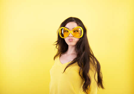 Foto de Excited comical young attractive woman with long hair and big funny glasses over yellow background. - Imagen libre de derechos