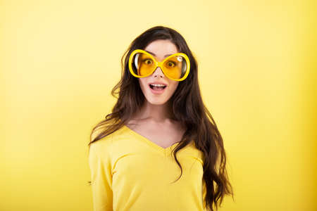 Foto de Happy smiling excited comical surprised young attractive woman with long flying hair and big funny glasses over yellow background. - Imagen libre de derechos