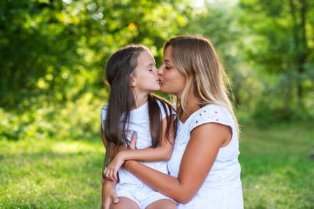 Photo pour Little girl hugs kissing her mother in summer forest nature outdoor. Portrait of mom and daughter wearing white clothes against summer greenery. Family, trust, kindness, maternity, parenthood, confidence, mother's love concept. - image libre de droit