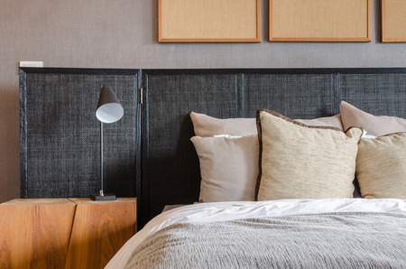 modern black bed with pillows and lamp in bedroom at home