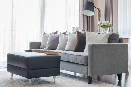 modern grey sofa with pillows and black table in living room at home