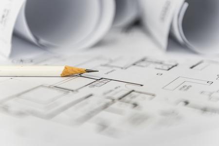 Foto de white pencil on architectural for construction drawings  with roll of blueprint - Imagen libre de derechos