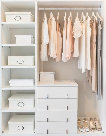 Photo pour white wardrobe on wooden floor with dress hanging on rail - image libre de droit