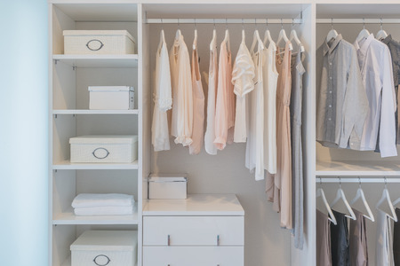 Photo pour clothes hanging on rail in white wardrobe with boxes - image libre de droit