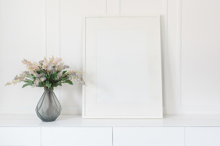 Photo pour glass vase of flower with white picture frame on white table - image libre de droit