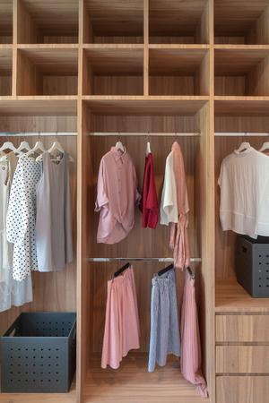 Photo pour modern closet with clothes hanging on rail, white wooden wardrobe, interior design concept - image libre de droit