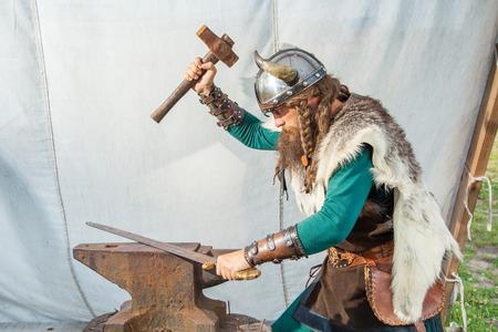 Strong viking is repairing his sword