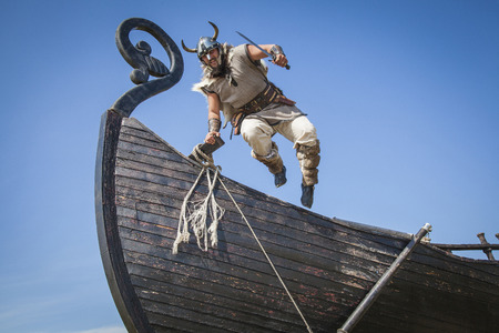 Photo for Strong Viking jumping from his ship to attack - Royalty Free Image