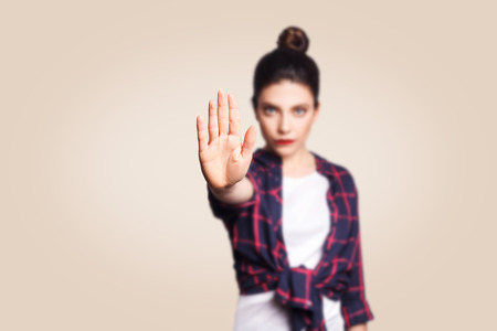 Young annoyed woman with bad attitude making stop gesture with her palm outward, saying no, expressing denial or restriction. Negative human emotions, feelings, body language. Selective focus on hand.