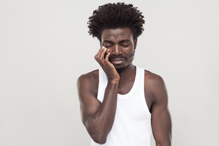 Closed eyes and cry. Unhappy afro man with souvarov mustache, cry and have depression. Indoor shot