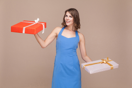 Holiday or birthday concept. Happiness woman holding two gifts boxes. Studio shot