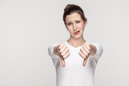 Unhappy woman demonstrate dislike sign. Studio shot, gray background