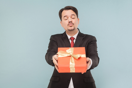 Happy man in black suit holding and kissing and giving red gift box. Studio shot, isolated on light blue background