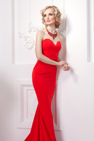 Fashion model in red dress, curly hairstyle and glamour jewelry. Indoor, studio shot