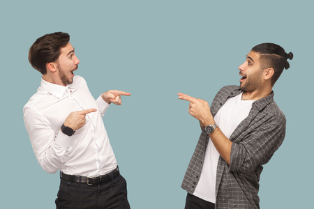 Foto de Is that you? profile side view of two handsome funny wondered bearded friends standing and pointing to each other with amazed face and asking. indoor studio shot, isolated on light blue background. - Imagen libre de derechos