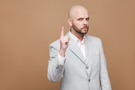 Foto de Hey you. Portrait of serious handsome middle aged bald bearded boss businessman in classic gray suit standing and looking at camera, warning. indoor studio shot, isolated on light brown background. - Imagen libre de derechos