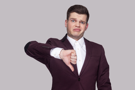 Photo pour Portrait of handsome confused young man in violet suit and white shirt, standing, looking at camera with thumbs down and unsatisfied face. indoor studio shot, isolated on grey background. - image libre de droit