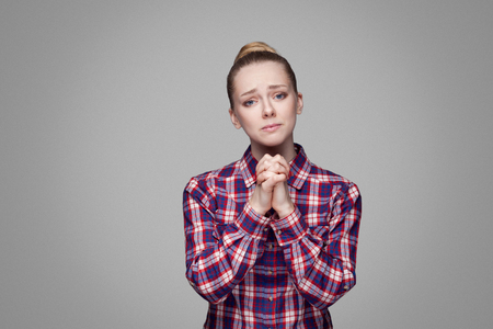 Photo for Please help me. beautiful blonde girl in red, pink checkered shirt, collected bun hairstyle standing and looking at camera with palm hands and begging. indoor studio shot. isolated on gray background - Royalty Free Image