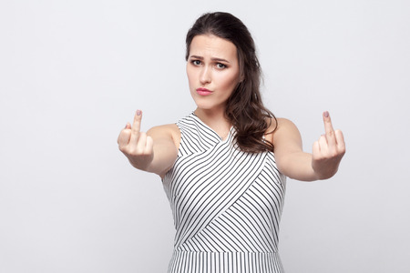 Foto für Portrait of angry young brunette woman with makeup and striped dress standing serious face and looking at camera and showing middle finger fuck sign. indoor studio shot, isolated on grey background. - Lizenzfreies Bild