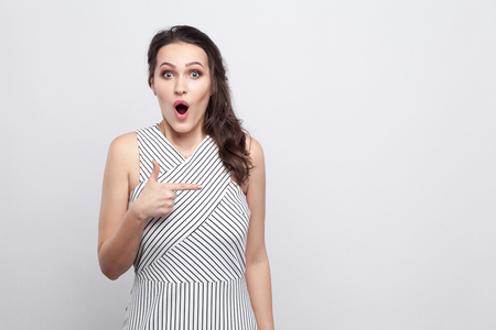 Photo pour Portrait of beautiful amazed young brunette woman in striped dress standing and looking at camera with surprised face and pointing at copyspace. indoor studio shot, isolated on grey background - image libre de droit