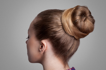 Foto de Profile side view closeup portrait of woman with creative elegant brown collected hairstyle, bun hair. indoor studio shot, isolated on grey background. - Imagen libre de derechos