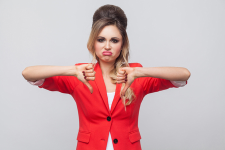 Photo pour Portrait of sad dissatisfied beautiful business lady with hairstyle and makeup in red fancy blazer, standing with thubms down and looking at camera. indoor studio shot, isolated on grey background. - image libre de droit