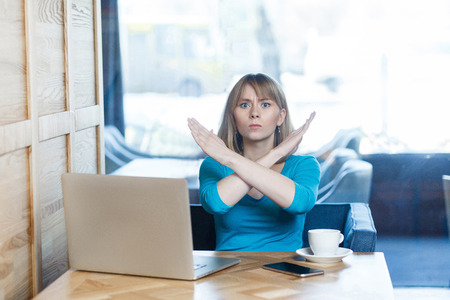 Foto de Enough! Portrait of warning aggressive young girl with blonde hair in t-shirt blouse are sitting in cafe and working on laptop and showing crossing raised arms like stop gesture. Indoor - Imagen libre de derechos
