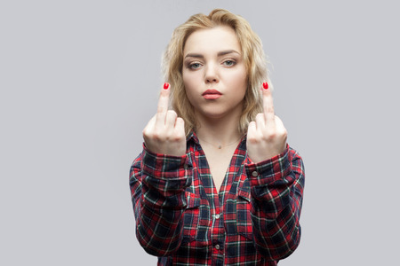 Foto de Portrait of serious young beautiful blonde woman in casual red checkered shirt standing and looking with poker face and middle finger fuck sign. indoor studio shot, isolated on grey background. - Imagen libre de derechos