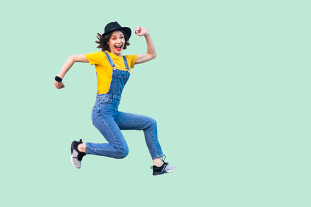 Portrait of happy carefree pretty young hipster girl in blue denim overalls, yellow shirt and black hat jumping, looking at camera and enjoying. indoor studio shot isolated on light green background.