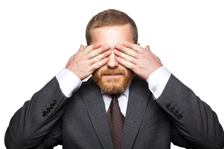 Photo pour Closeup portrait of handsome businessman with facial beard in black suit standing and closed his eyes and dont want to looking. indoor studio shot isolated on white background. - image libre de droit