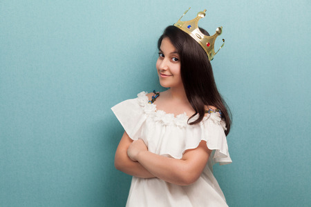 Portrait of young satisfied arrogance beautiful princess brunette girl wear in white dress and golden diadem crown crossed arms and looking at camera. Indoor, isolated, studio shot, blue background
