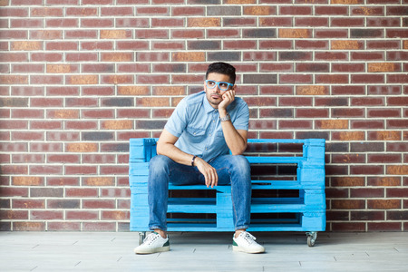 Photo for Full length portrait of thoughtful serious handsome young bearded man in casual style and eyeglasses sitting on blue wooden pallet, thinking and looking away. indoor studio shot on brown brick wall. - Royalty Free Image