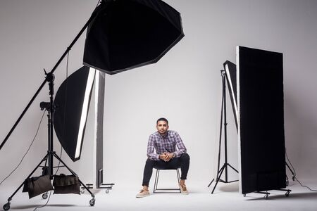 Photo pour Professional photography studio showing behind the scenes lights. fashion handsome young man model at studio in the light flashes, sitting and looking at camera. indoor studio shot on grey background. - image libre de droit