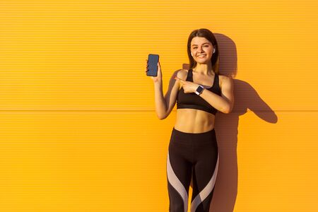 Photo pour Young satisfied beautiful sporty woman in black sportwear standing near orange wall background and holding phone, pointing finger with toothy smile, looking at camera, outdoor on summer, sunshine - image libre de droit