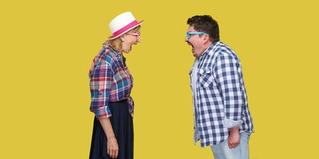 Photo pour Side view portrait of couple of friends, adult man and woman in casual checkered shirt standing to each other and screaming with opened mouth. Indoor, isolated, studio shot, yellow background - image libre de droit