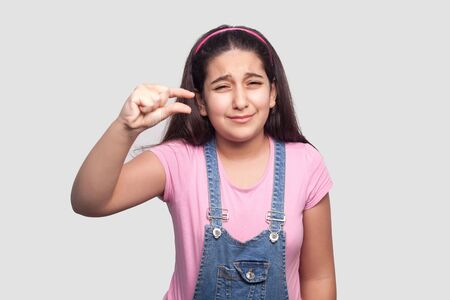 Foto de I need few more. Portrait of worry brunette young girl in pink t-shirt and blue overalls standing with small gesture with fingers and looking at camera. indoor studio shot, isolated on gray background - Imagen libre de derechos