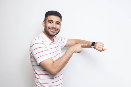 Photo for Good result and ontime. Happy handsome bearded young man in striped t-shirt standing, showing his smart watch and looking at camera with toothy smile. indoor studio shot, isolated on white background. - Royalty Free Image